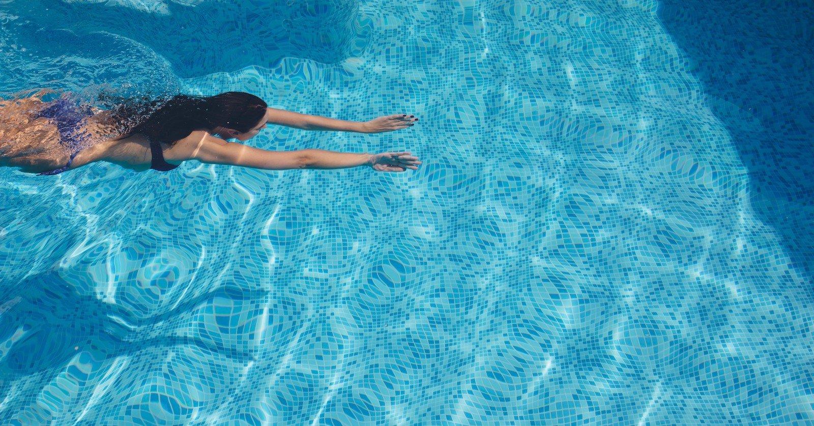 girl swimming across pool copy
